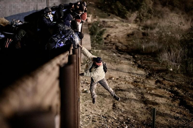 A migrant jumps the border fence to get into the U.S.