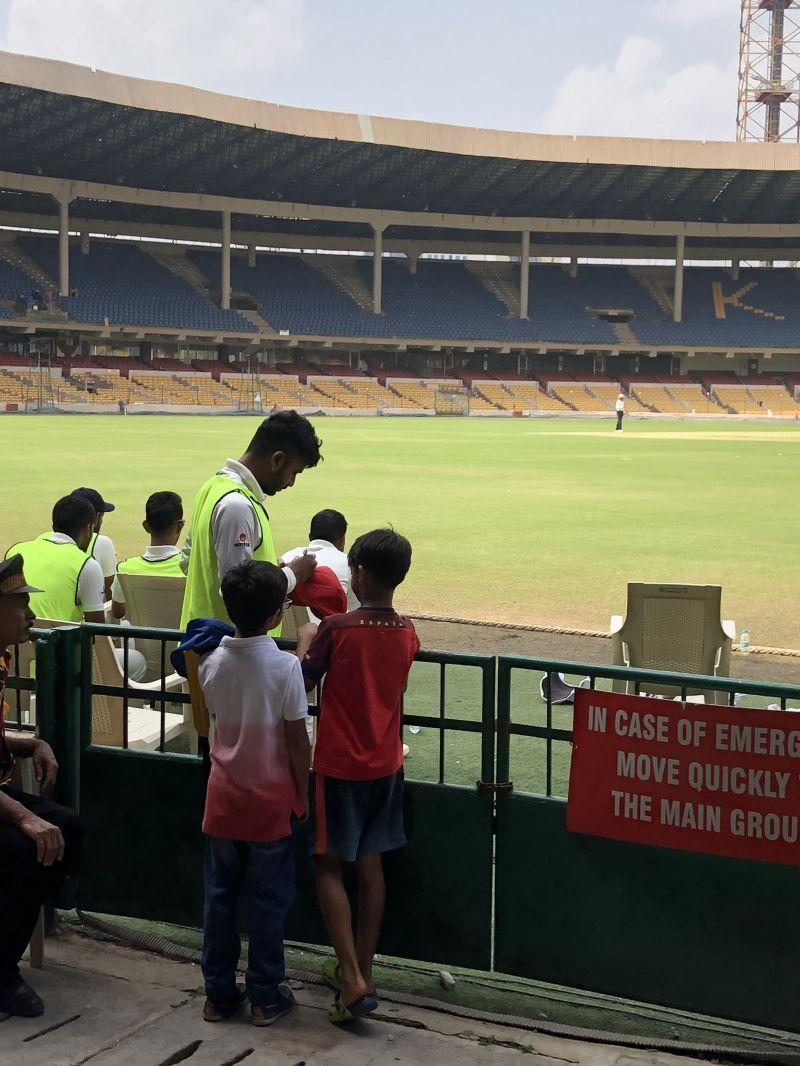 Two enthusiastic kids taking an autograph from the Karnataka players as the security looks on