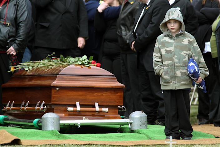 """FILE - In this Monday, April 2, 2012 file photo, Nicholas Weichel, son of Rhode Island National Guard Sgt. Dennis Weichel Jr., who was killed in Afghanistan, stands next to his father's casket during funeral services at the state Veterans Cemetery in Exeter, R.I.. Weichel Jr., was struck and killed by an armored vehicle March 22 in Afghanistan while saving an Afghan boy. It was once President Barack Obama's """"war of necessity."""" Now, it's America's forgotten war. The Afghan conflict generates barely a whisper on the U.S. presidential campaign trail. It's not a hot topic at the office water cooler or in the halls of Congress _ even though 88,000 American troops are still fighting here and dying at a rate of one a day.(AP Photo/Stew Milne, File)"""