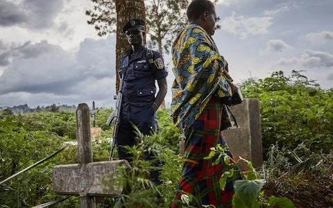 A police officer guards the funeral of Ebola victims in Butembo - Credit: HUGH KINSELLA CUNNINGHAM/EPA-EFE/REX