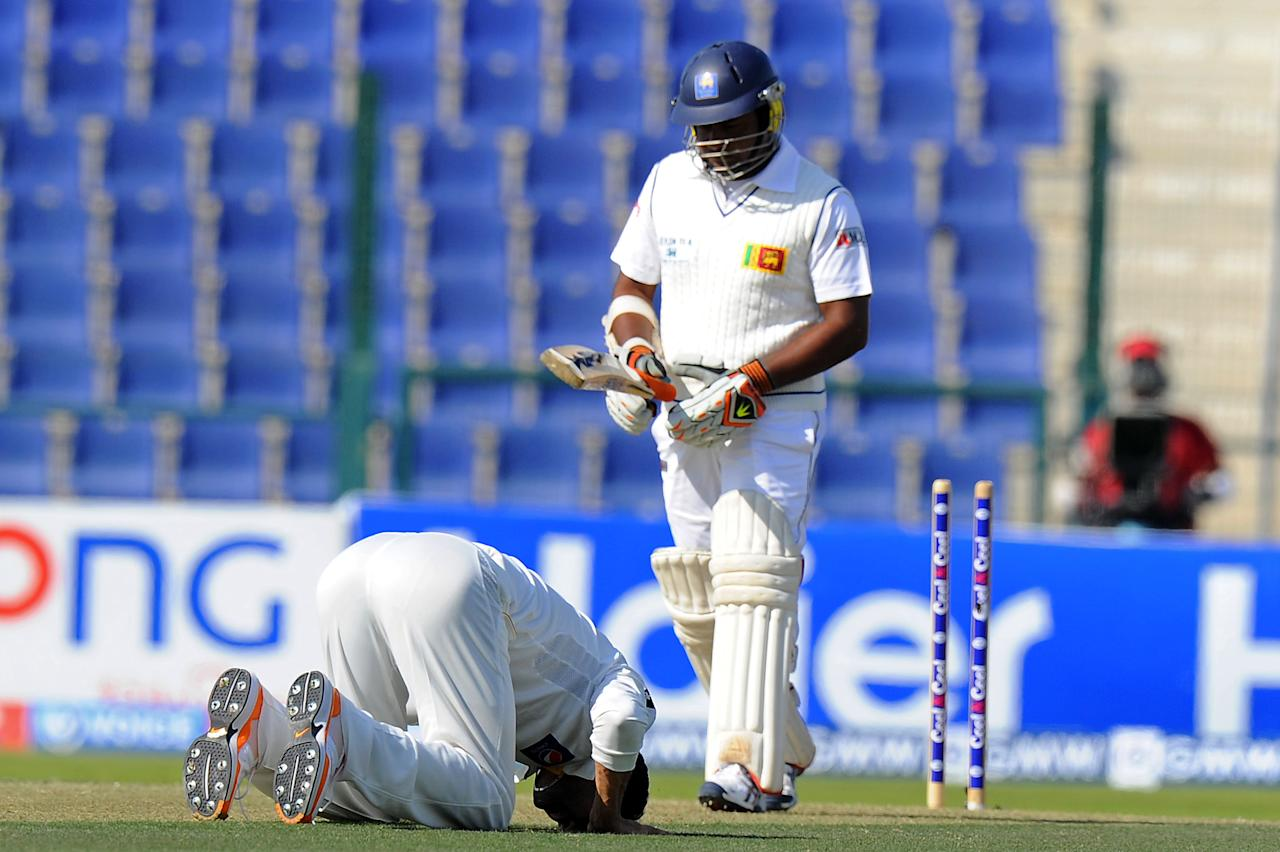 Pakistan bowler Junaid Khan (L) gestures in prayer after dismissing Sri Lankan batsman Rangana Herath (R) during the opening day of their first cricket Test match between Pakistan and Sri Lanka at the Sheikh Zayed Stadium in Abu Dhabi on December 31, 2013. AFP PHOTO/Ishara S. KODIKARA
