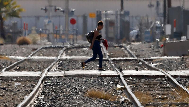 While the heat waves rise up from the ground, a woman crosses the railroad tracks as temperatures climb past 112 degrees on July 5, 2018, in Phoenix.