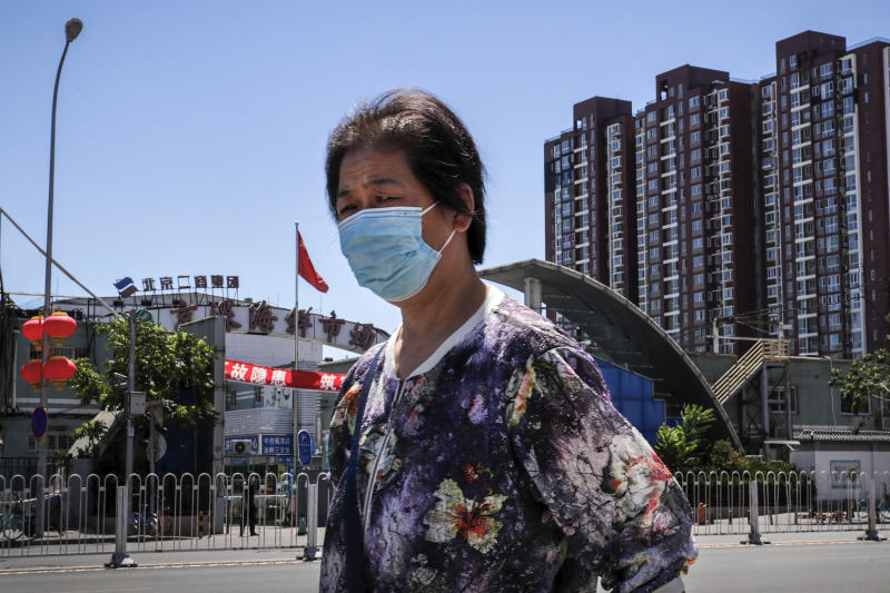 A woman wearing a protective face mask to help curb the spread of the new coronavirus walks by the seafood wholesale market closed for inspection in Beijing, Sunday, June 14, 2020. China is reporting its highest daily total of coronavirus cases in two months after the capital's biggest wholesale food market was shut down following a resurgence in local infections. (AP Photo/Andy Wong)