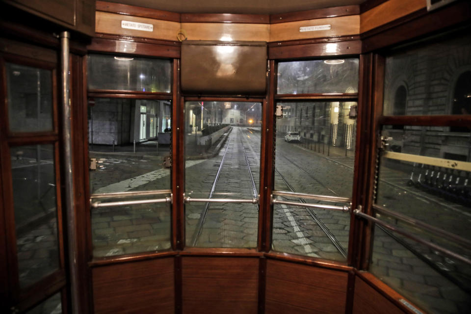 An empty street is seen from a tram streetcar window, in Milan, northern Italy, early Sunday, Oct. 25, 2020. Since the 11 p.m.-5 a.m. curfew took effect last Thursday, people can only move around during those hours for reasons of work, health or necessity. (AP Photo/Luca Bruno)