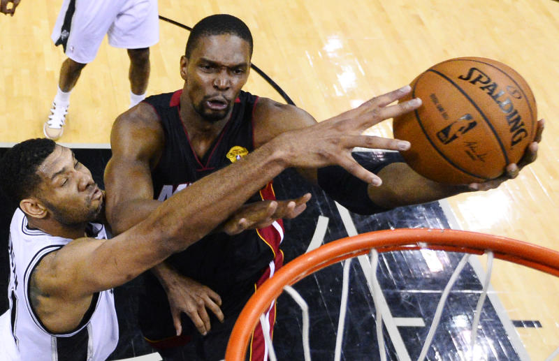 Miami Heat center Chris Bosh shoots as San Antonio Spurs forward Tim Duncan, left, defends during the first half in Game 2 of the NBA basketball finals on Saturday, Nov. 8, 2014, in San Antonio