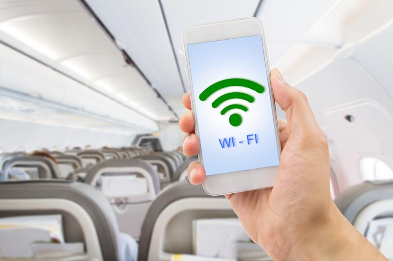 A man holding up a smartphone with the word and icon for Wi-Fi on the screen while inside an airplane.