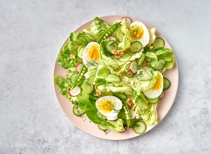 breakfast salad with eggs on pink plate and marble background