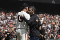 San Francisco Giants manager Bruce Bochy, left, hugs his son, former Giants pitcher Brett Bochy, after the ceremonial first pitch before a baseball game between the Giants and the Los Angeles Dodgers in San Francisco, Sunday, Sept. 29, 2019. (AP Photo/Jeff Chiu)
