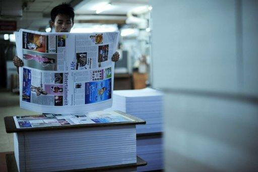 A Myanmar worker checks the printed sheets of a local journal at a printing house in Yangon on August 20, 2012. Journalists in Myanmar still face repressive laws that can land them in prison and say they will not stop fighting for greater freedom