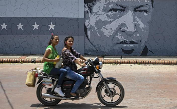 Two girls with extra gas cans ride a motorcycle past a mural with an image of late Venezuelan President Hugo Chavez in Sabaneta, Barinas State (AFP Photo/Yuri CORTEZ)
