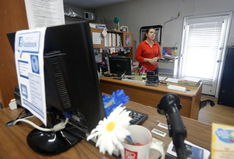 Library Director Jennifer Ramirez advises a visitor that she is unable to assist him with his request because most of the computers at the public library in Wilmer, Texas, were not working on Thursday, Aug. 22, 2019. Cyberattacks that recently crippled nearly two dozen Texas cities have put other local governments on guard. (AP Photo/Tony Gutierrez)