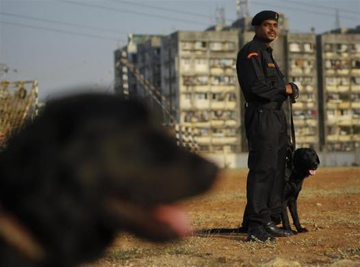 An Indian National Security Guard (NSG) commando stands with his sniffer dog during the inauguration ceremony of their regional hub in Mumbai February 23, 2012.