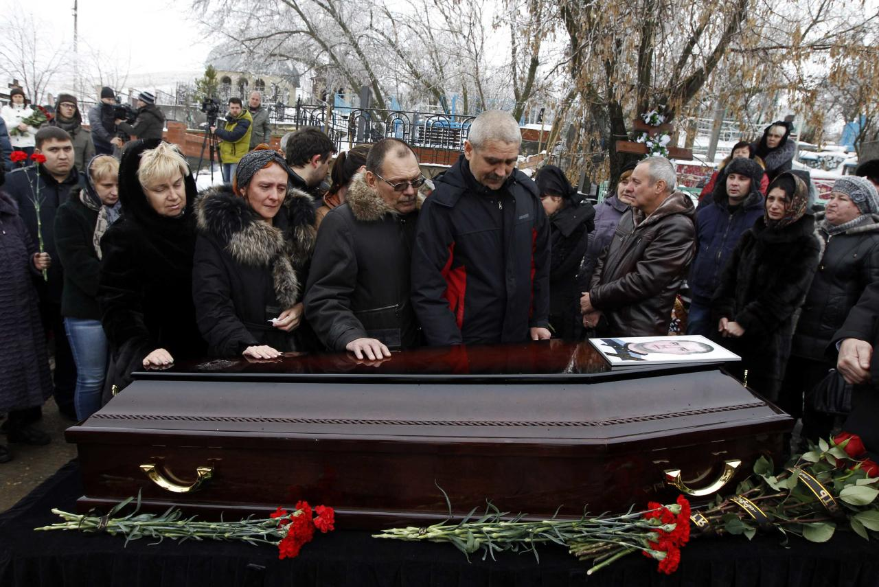 Relatives gather around the coffin of a victim of an explosion at a funeral in Volgograd December 31, 2013. Police detained dozens of people on Tuesday in sweeps through the Russian city of Volgograd after two deadly attacks in less than 24 hours that raised security fears ahead of the Winter Olympics. REUTERS/Vasily Fedosenko (RUSSIA - Tags: CIVIL UNREST CRIME LAW TRANSPORT)