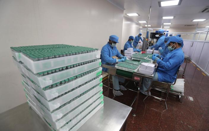 Employees pack boxes containing vials of AstraZeneca's COVISHIELD vaccine at the Serum Institute of India - Rafiq Maqbool /AP