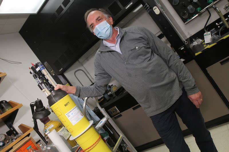 Johnson stands next to a robotic ocean float in a laboratory at the Monterey Bay Aquarium Research Institute in Moss Landing