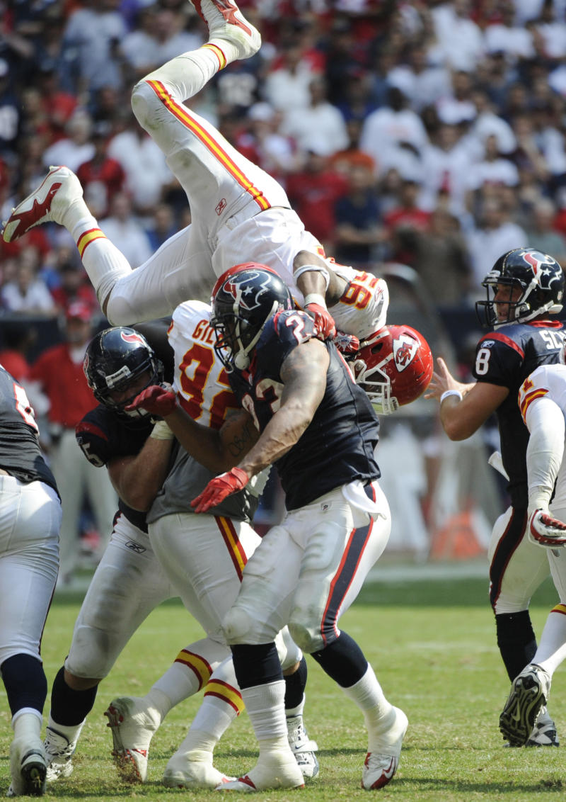 Kansas City Chiefs linebacker Derrick Johnson (56) is upended by Houston Texans Arian Foster (23) and Chris Myers (55) as he tries to reach Texans quarterback Matt Schaub (8), right, during the fourth quarter of an NFL football game Sunday, Oct. 17, 2010, in Houston. (AP Photo/Dave Einsel)
