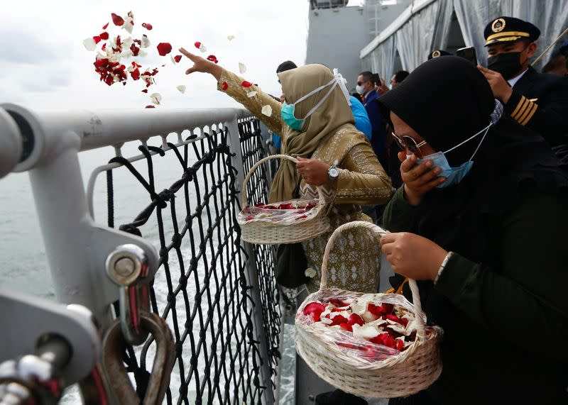 Family members of the passengers of Sriwijaya Air flight SJ 182, which crashed into the sea, react while throwing flowers and petals from the deck of Indonesia's Naval ship KRI Semarang as they visit the site of the crash to pay their tribute