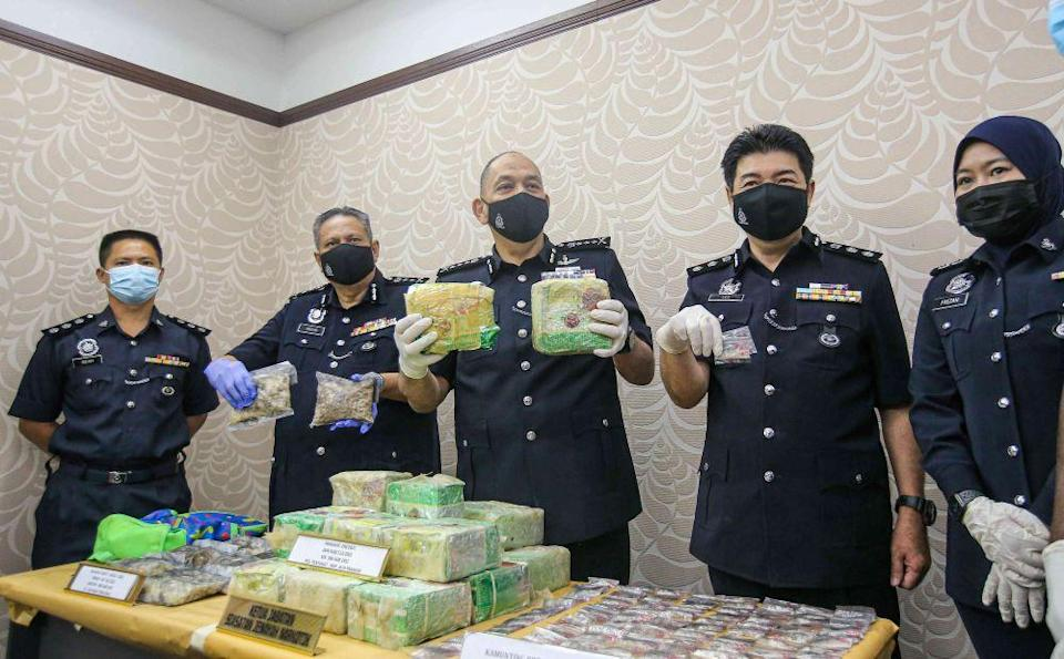 Perak police chief commissioner Datuk Mior Faridalathrash Wahid (centr) holds up drugs seized at the state police headquarters in Ipoh February 26, 2021. — Picture by Farhan Najib