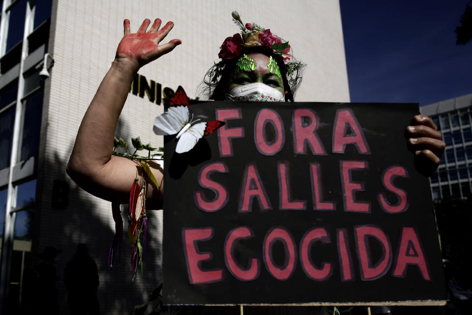 """An activist holds a poster with a message that reads in Portuguese: """"Out Salles Ecocida"""" directed at the Environment Minister Ricardo Salles, during a protest against the government's environmental policies, marking World Environment Day, in Brasilia, Brazil, Saturday, June 5, 2021. (AP Photo/Eraldo Peres)"""