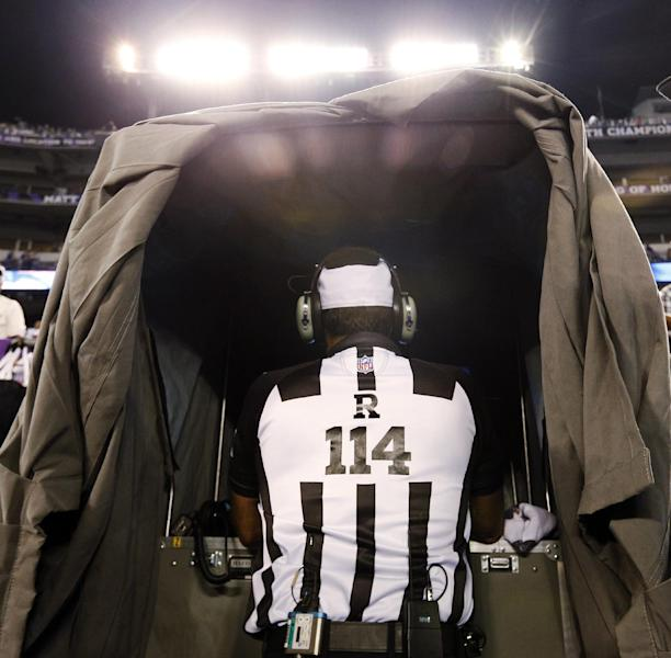 Referee Gene Steratore looks over the instant replay monitor before an NFL football game between the Baltimore Ravens and Cleveland Browns in Baltimore, Thursday, Sept. 27, 2012. (AP Photo/Patrick Semansky)