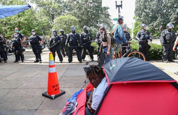 PHOTO: A person looks out of their tent as Washington, D.C. Metropolitan Police officers approach to clear the Black Lives Matter Plaza area in front of St. John's Episcopal Church during protests near the White House in Washington, June 23, 2020. (Tom Brenner/Reuters)