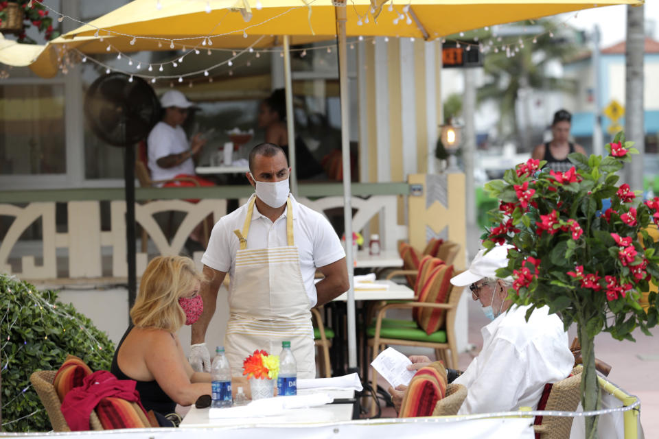 Jeffrey Holinka wears a protective face mask as he waits to receive an order at the On Ocean 7 Cafe along Ocean Drive in Miami Beach, Fla. during the new coronavirus pandemic, Wednesday, May 27, 2020. Ocean Drive was closed to traffic as restaurants in Miami Beach reopened Wednesday after being closed to mitigate the spread of the coronavirus. (AP Photo/Lynne Sladky)