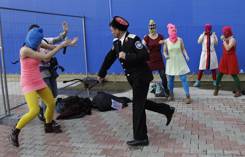 A Cossack militiaman attacks Nadezhda Tolokonnikova and a photographer as she and fellow members of the punk group Pussy Riot, including Maria Alekhina, center, in the pink balaclava, stage a protest performance in Sochi, Russia, on Wednesday, Feb. 19, 2014. The group had gathered in a downtown Sochi restaurant, about 30km (21miles) from where the Winter Olympics are being held. They ran out of the restaurant wearing brightly colored clothes and ski masks and were set upon by about a dozen Cossacks, who are used by police authorities in Russia to patrol the streets. (AP Photo/Morry Gash)