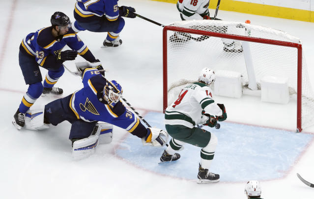 Minnesota Wild's Joel Eriksson Ek (14), of Sweden, scores past St. Louis Blues goaltender Chad Johnson and Jordan Schmaltz (43) during the second period of an NHL hockey game Sunday, Nov. 11, 2018, in St. Louis. (AP Photo/Jeff Roberson)