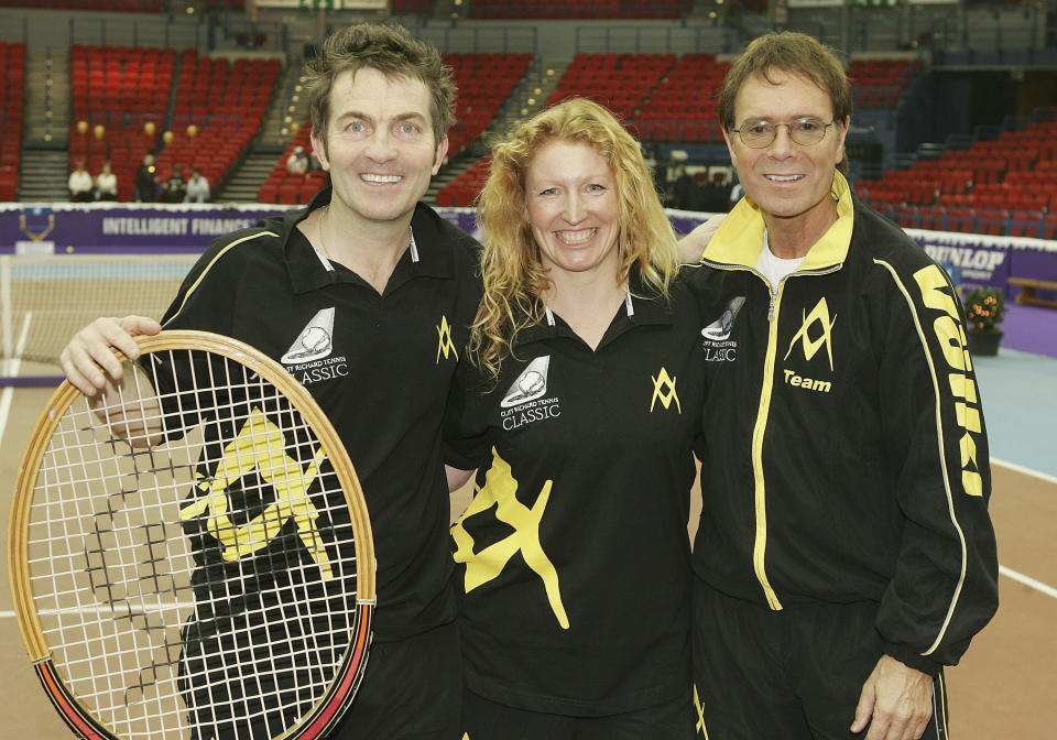 "BIRMINGHAM, ENGLAND - DECEMBER 18: Bradley Walsh, Charlie Dimmock and Cliff Richard pose at a photocall ahead of the ""Intelligent Finance Cliff Richard Tennis Classic"" at Birmingham National Indoor Arena on December 18, 2004 in Birmingham, England. The annual tournament raises money for the Cliff Richard Tennis Foundation, which introduces children across the country to the game. (Photo by MJ Kim/Getty Images)"