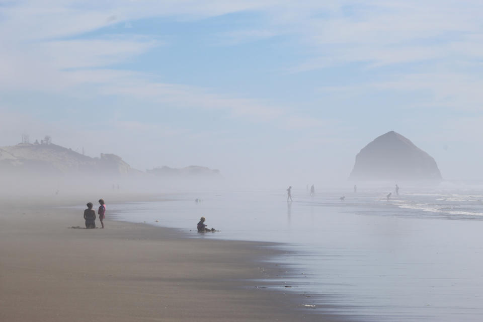 FILE - People walk on the beach at Tierra del Mar, Ore., on, Aug. 17, 2020. The Oregon Coast is featured in a collection of mini-essays by American writers published online by the Frommer's guidebook company about places they believe helped shape and define America. (AP Photo/Andrew Selsky, File)
