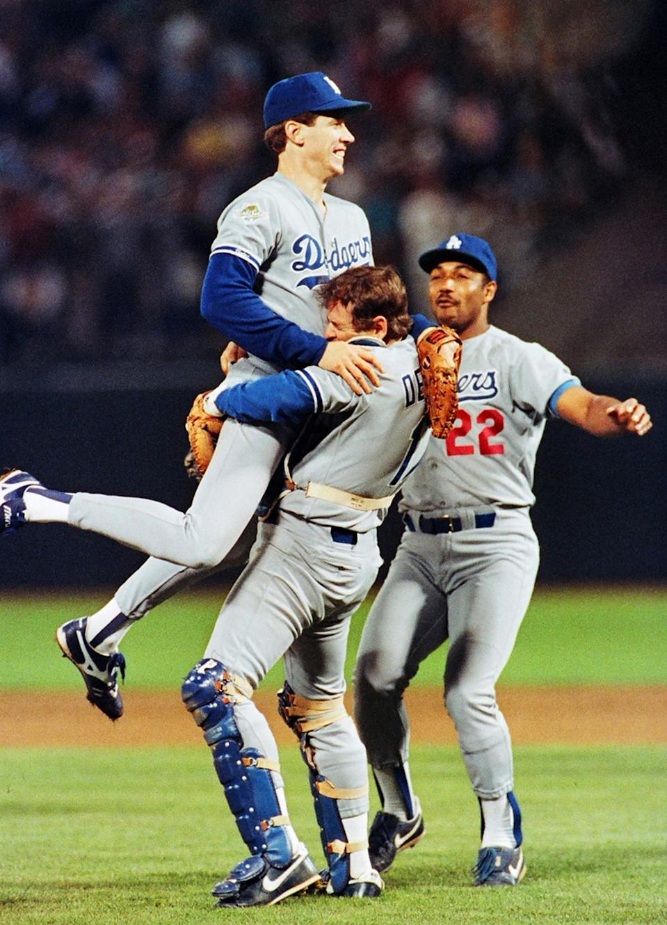 Dodgers starting pitcher Orel Hershiser leaps into the arms of catcher Rick Dempsey to celebrate title.