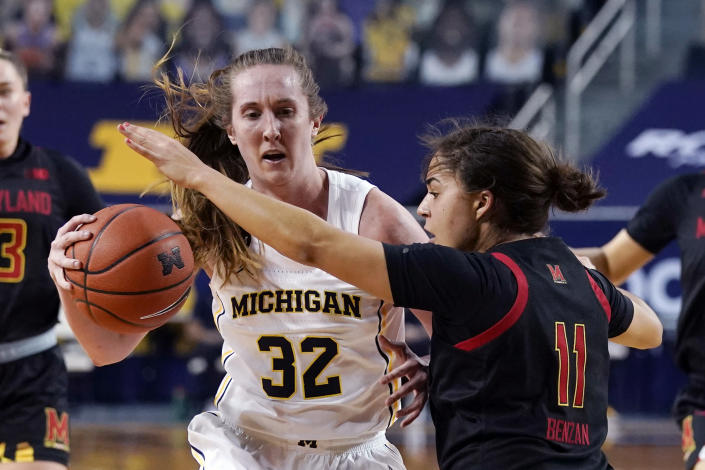 Michigan guard Leigha Brown (32) drives on Maryland guard Katie Benzan (11) during the first half of an NCAA college basketball game, Thursday, March 4, 2021, in Ann Arbor, Mich. (AP Photo/Carlos Osorio)