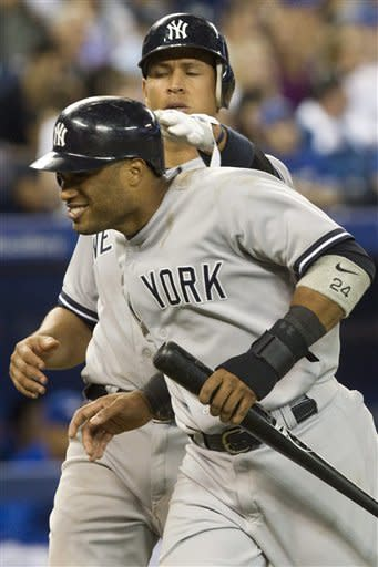 New York Yankees Alex Rodriguez (left) pats Robinson Cano on the back after the pair scored on a single by Curtis Granderson against Toronto Blue Jays during ninth inning of a baseball game in Toronto on Sunday, Sept. 30 , 2012. (AP Photo/The Canadian Press, Chris Young)