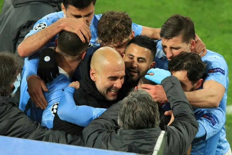Manchester City players and coach Pep Guardiola celebrate as they beat Borussia Dortmund to reach the Champions League semi-finals for the first time since 2016