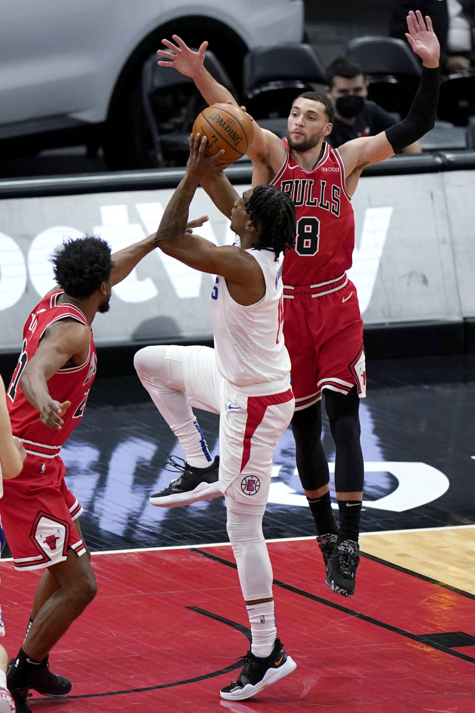 Los Angeles Clippers guard Terance Mann, center, goes up for a shot between Chicago Bulls forward Thaddeus Young, left, and guard Zach LaVine during the first half of an NBA basketball game in Chicago, Friday, Feb. 12, 2021. (AP Photo/Nam Y. Huh)