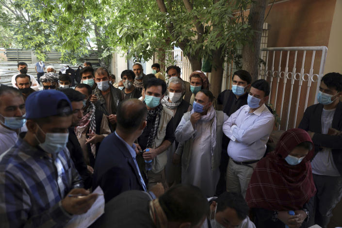 """Residents, wearing face masks to help curb the spread of the coronavirus, line up to receive the Sinopharm COVID-19 vaccine at a vaccination center, in Kabul, Afghanistan, Wednesday, June 16, 2021. In Afghanistan, where a surge threatens to overwhelm a war-battered health system, 700,000 doses donated by China arrived over the weekend, and within hours, """"people were fighting with each other to get to the front of the line,"""" said Health Ministry spokesman Dr. Ghulam Dastigir Nazari. (AP Photo/Rahmat Gul)"""
