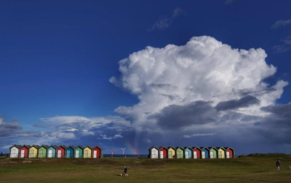 A rainbow appears behind the Blyth beach huts in Northumberland (PA) (PA Wire)