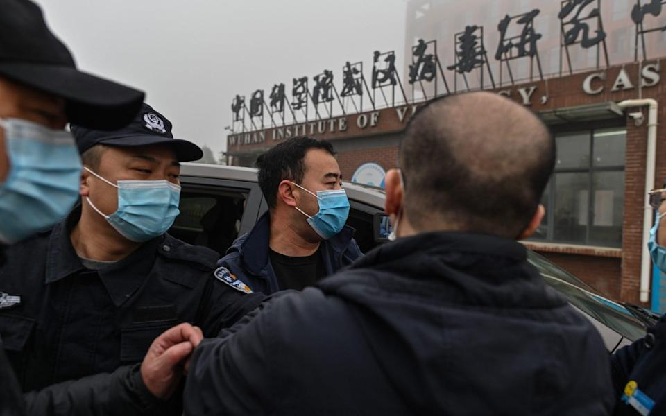 Security personnel are seen as members of the World Health Organization (WHO) team investigating the origins of the COVID-19 coronavirus, arrive at the Wuhan Institute of Virology in Wuhan, in China's central Hubei province on February 3, 2021 - HECTOR RETAMAL /AFP