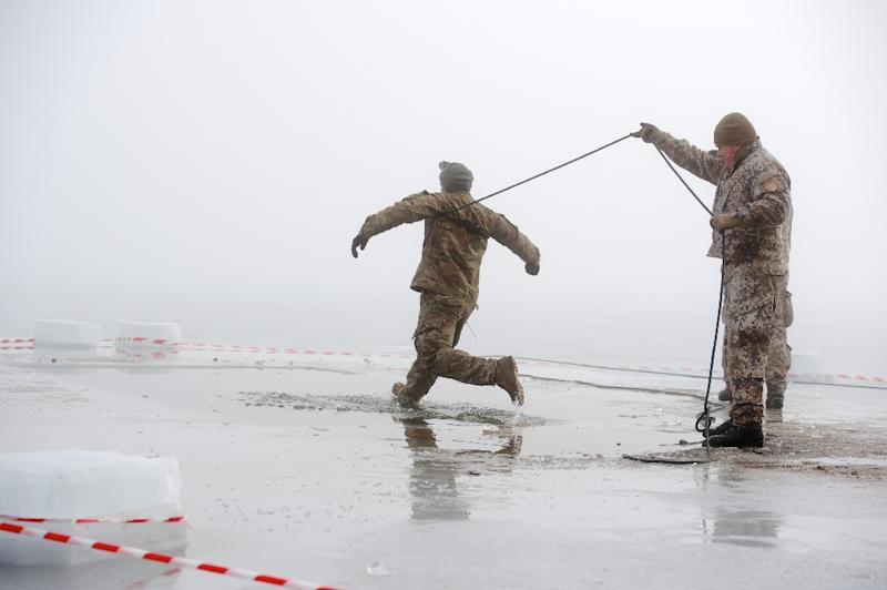 Soldiers practice an ice plunge exercise during a training with Latvian, US and Canadian soldiers at the Adazi military training area in Latvia on February 26, 2015 (AFP Photo/Ilmars Znotins)