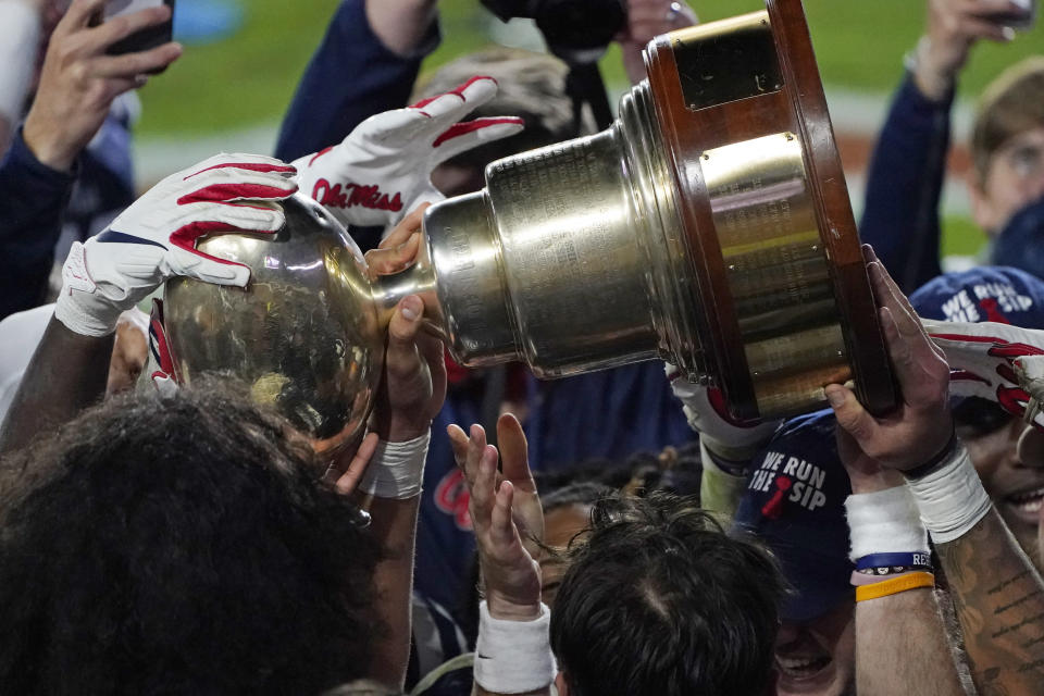 Mississippi players hoist the Egg Bowl trophy as they celebrate a win over Mississippi State in an NCAA college football game, Saturday, Nov. 28, 2020, in Oxford, Miss. (AP Photo/Rogelio V. Solis)