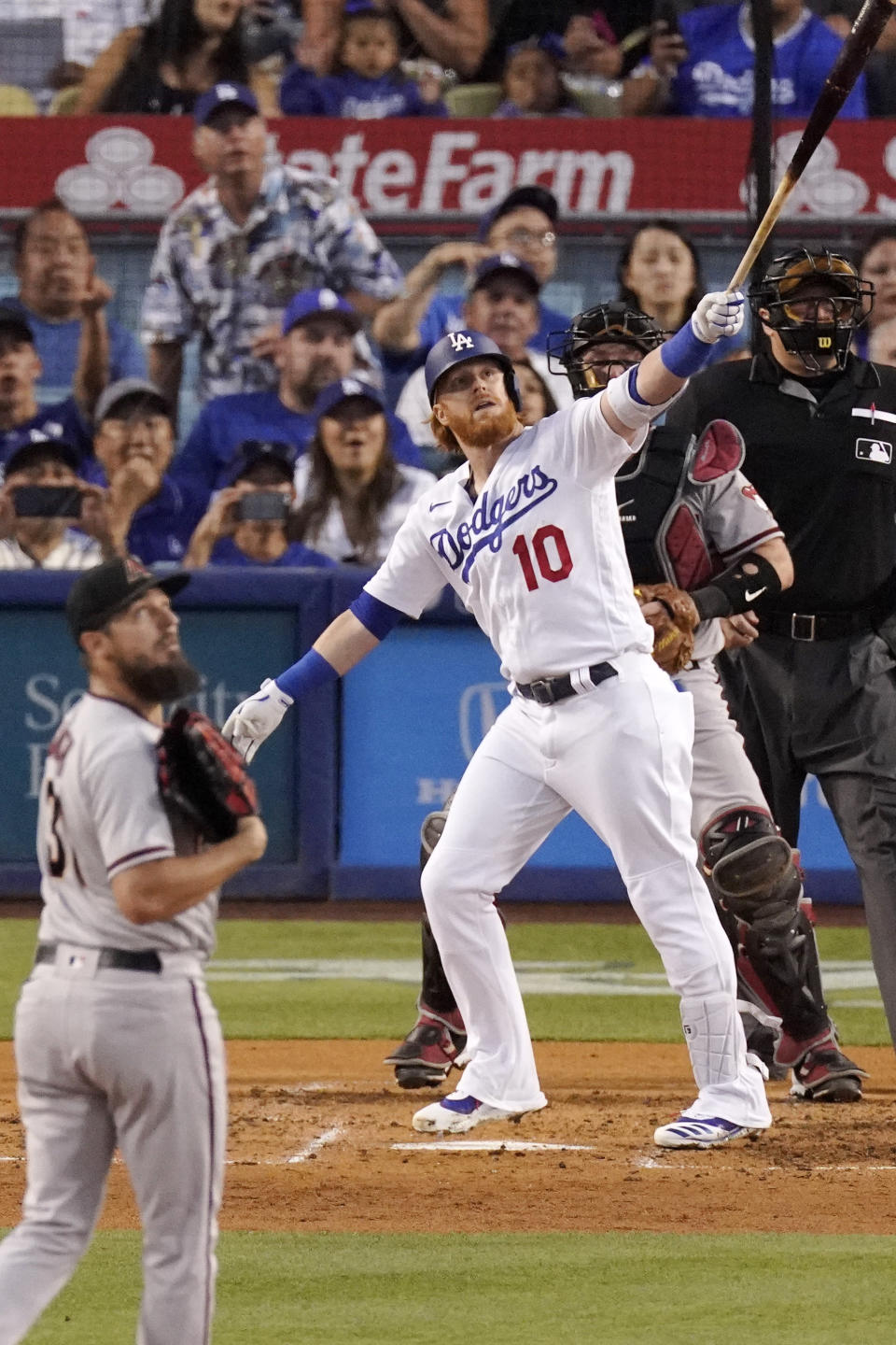 Los Angeles Dodgers' Justin Turner, second from left, hits a grand slam as Arizona Diamondbacks starting pitcher Caleb Smith, left, and catcher Bryan Holaday, second from right, watch along with home plate umpire Tony Randazzo during the second inning of a baseball game Saturday, July 10, 2021, in Los Angeles. (AP Photo/Mark J. Terrill)