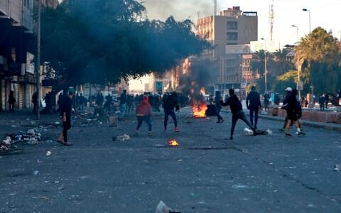 Protesters set fire to close a street during clashes between security forces and anti-government protesters near Baghdad's Khilani square - Credit: AP