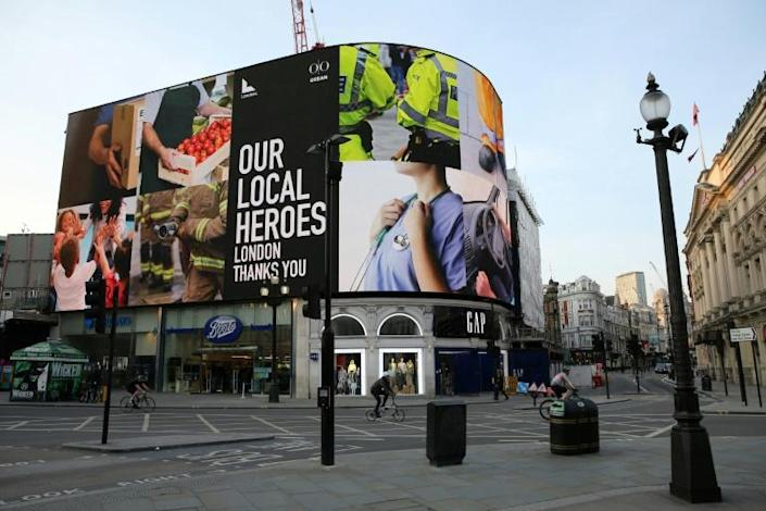 "A display of images in Piccadilly Circus in central London accompanies a message of support for ""our local heroes"" working to combat the coronavirus epidemic (AFP Photo/ISABEL INFANTES)"