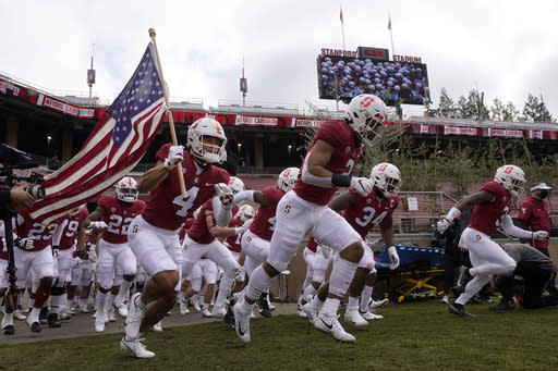 Stanford players run onto the field before an NCAA college football game against Colorado in Stanford, Calif., Saturday, Nov. 14, 2020. (AP Photo/Jeff Chiu)