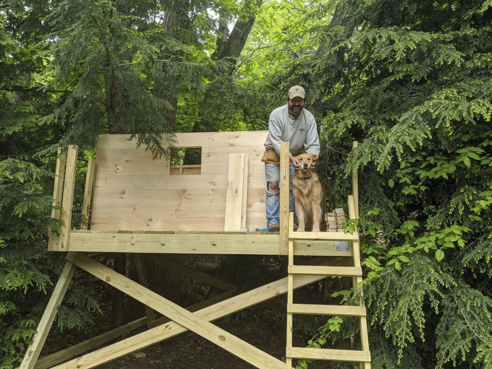 This photo taken by Nanci Butler in 2020 shows her husband, Ethan, in the backyard treehouse they built during the Covid-19 pandemic lockdown. About three months after it was built, an oak tree fell on top of the treehouse and demolished it. (Nanci Butler via AP)