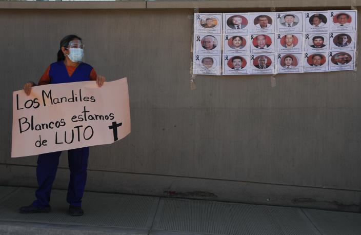 """A health worker holds a sign that reads in Spanish: """"The white aprons, we're in mourning"""" during a protest outside Petrolero Obrajes Hospital in La Paz, Bolivia, Wednesday, Jan. 27, 2021. Health workers want Bolivia's President Luis Arce to declare a quarantine to reduce the contagion of COVID-19 that has sickened doctors and filled hospitals' intensive care units. (AP Photo/Juan Karita)"""