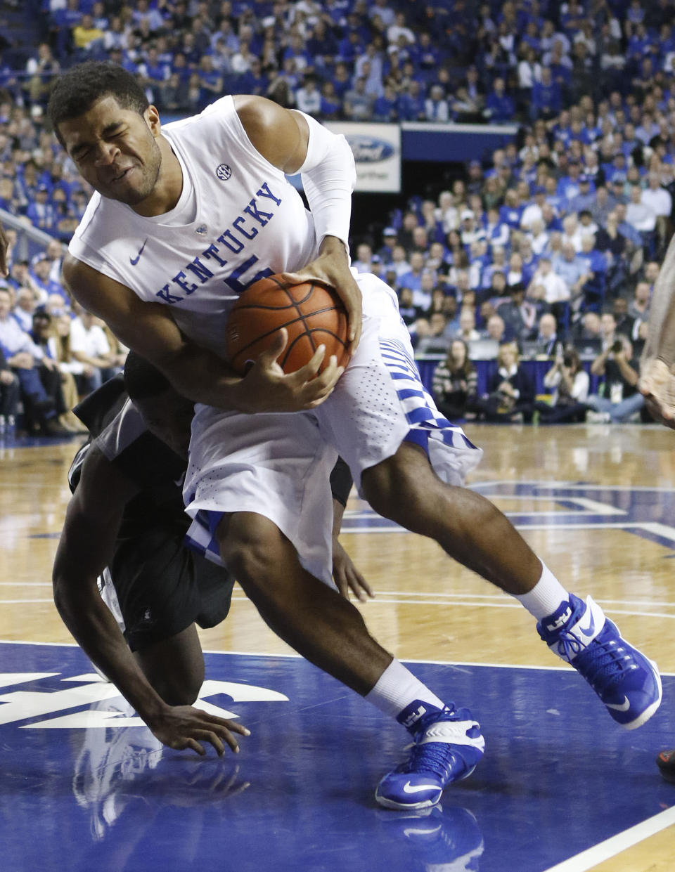 Kentucky's Andrew Harrison, top, is fouled by Providence's Kris Dunn during the second half of an NCAA college basketball game, Sunday, Nov. 30, 2014, in Lexington, Ky. Kentucky won 58-38. (AP Photo/James Crisp)