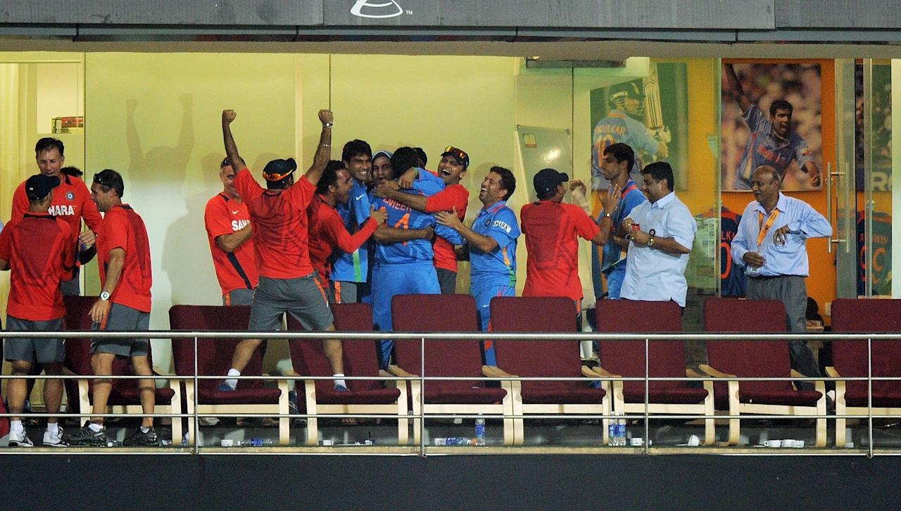 Indian cricketers and coaching staff celebrate after beating Sri Lanka during the ICC Cricket World Cup 2011 final match at The Wankhede Stadium in Mumbai on April 2, 2011. India beat Sri Lanka by six wickets.  AFP PHOTO/MANAN VATSYAYANA (Photo credit should read MANAN VATSYAYANA/AFP/Getty Images)