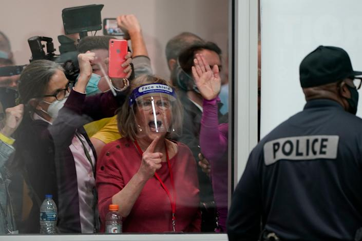 Election challengers yell as they look through the windows of the central counting board as police were helping to keep additional challengers from entering due to overcrowding, in Detroit, on November 4, 2020 (AP)