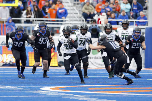 Hawaii running back Miles Reed, center, breaks away from the Boise State defense on a 25 yard run during the first half of an NCAA college football game for the Mountain West Championship Saturday, Dec. 7, 2019, in Boise, Idaho. (AP Photo/Steve Conner)